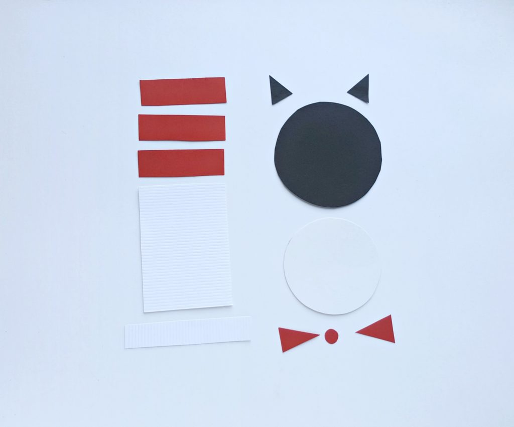 Coloured paper cut out in the template shapes for the Cat in the Hat.