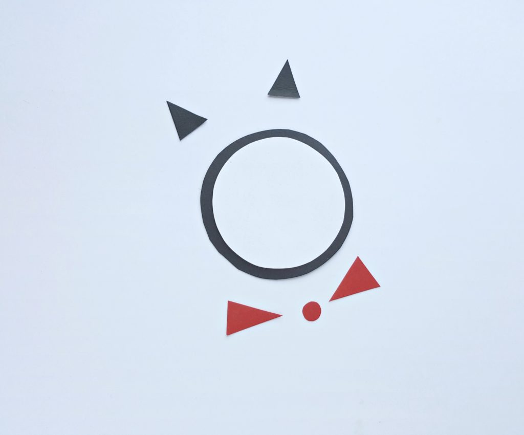 A white circle is pasted onto a black circle and the Cat in the Hat's ears and bow tie are being assembled.
