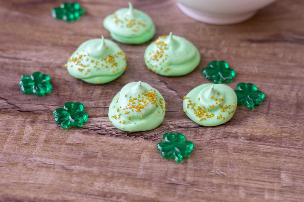 Close up of finished St. Patrick's meringues on wood tabletop with decorative 4-leaf clovers.