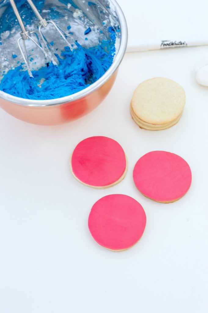 Icing is added to sugar cookies and red fondant circle is added on top.