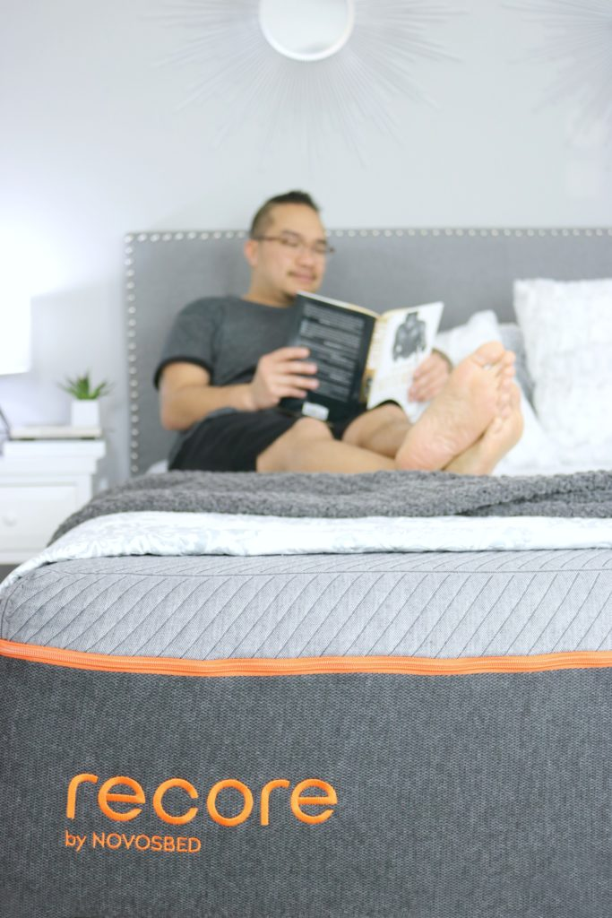 Darasak reads a book in bed while relaxing on his new Recore mattress.