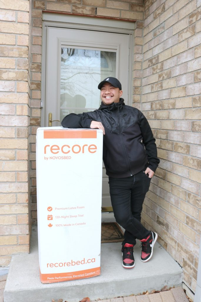 Darasak smiling and standing next to the Recore by Novosbed mattress delivery.