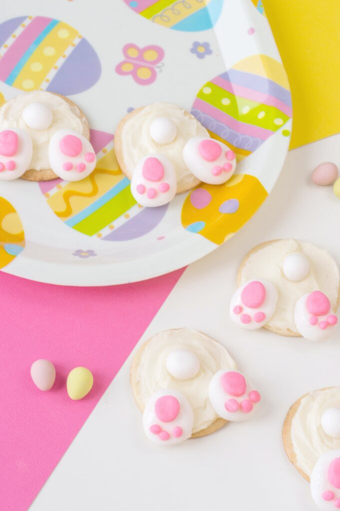 4 Bunny Bum cookies are shown on a pink, yellow, and white background. As well as on Easter plate.