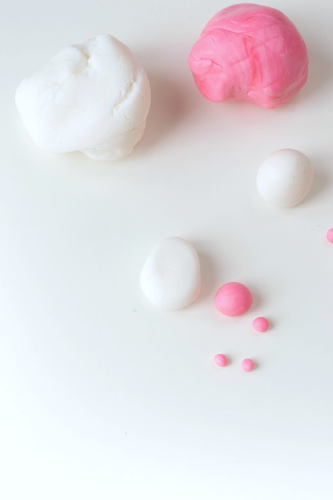 Pink and white fondant balls being rolled into bunny bums.