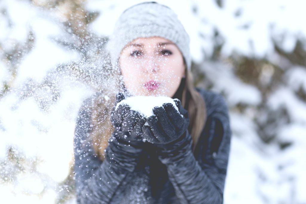 Girl blows a handful of snow from hands and towards the camera.