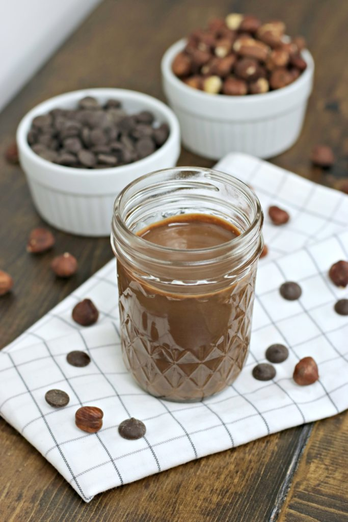8 oz. mason jar filled with homemade hazelnut spread. It is placed on a napkin and surrounded my ramekins of ingredients.