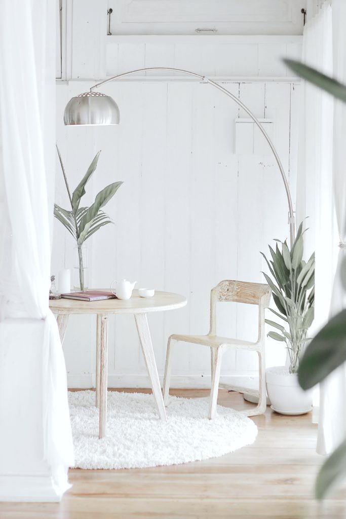Neutral living space with green plants, neutral wood table and chair and silver lamp.