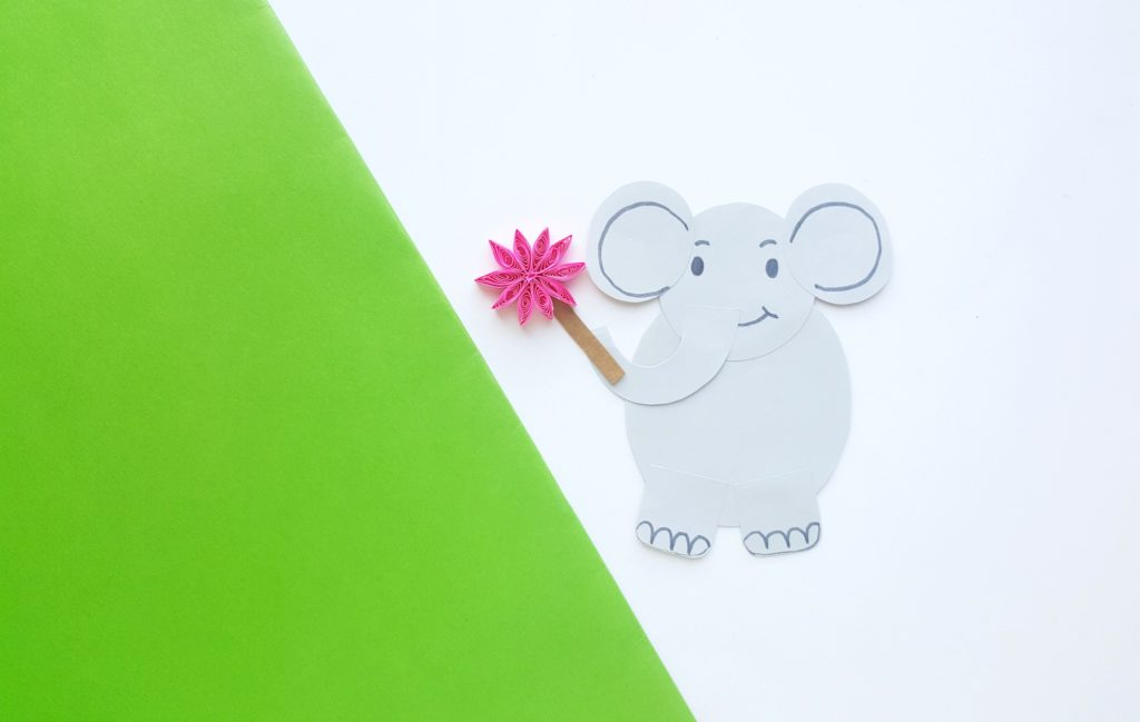 Horton now has a face, ears and is holding the pink flower. He's against a green and white background that looks like he's climbing a hill.
