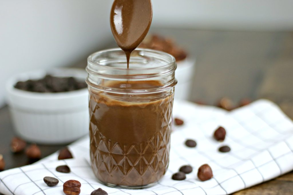 Freshly poured hazelnut spread into 8 oz. mason jar, a spoon is pulled out and it is dripping with chocolate.