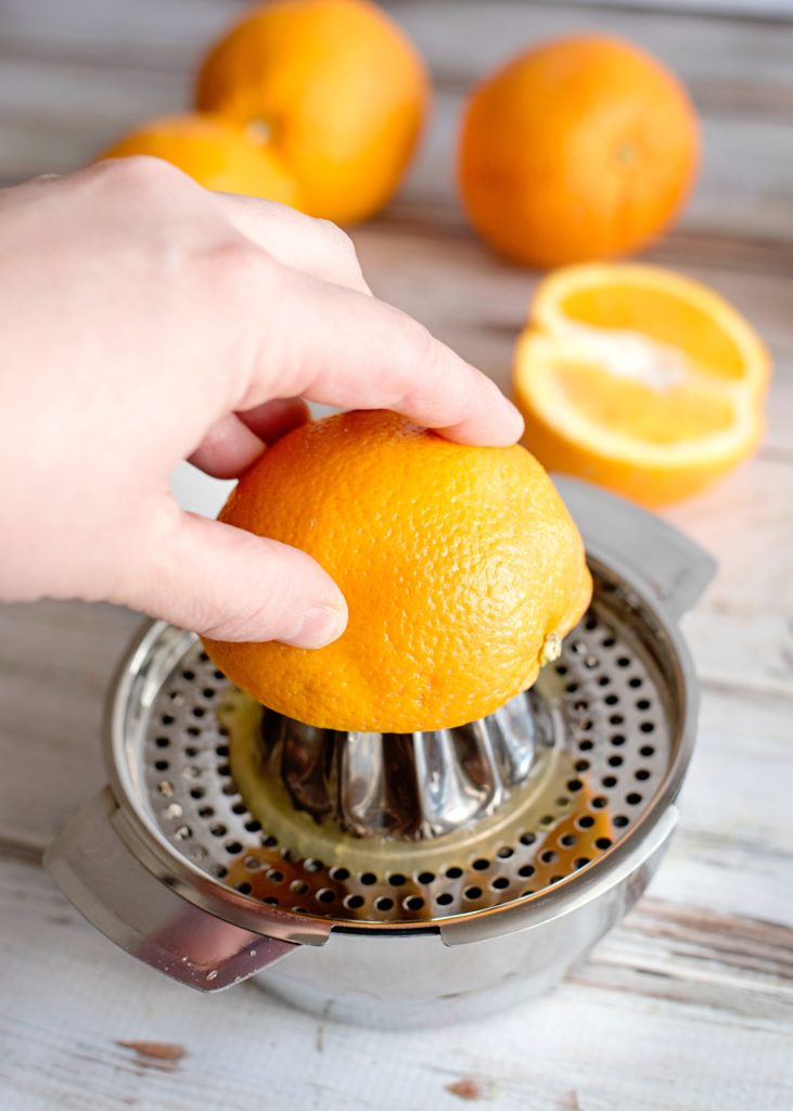 Orange being squeezed for juice.