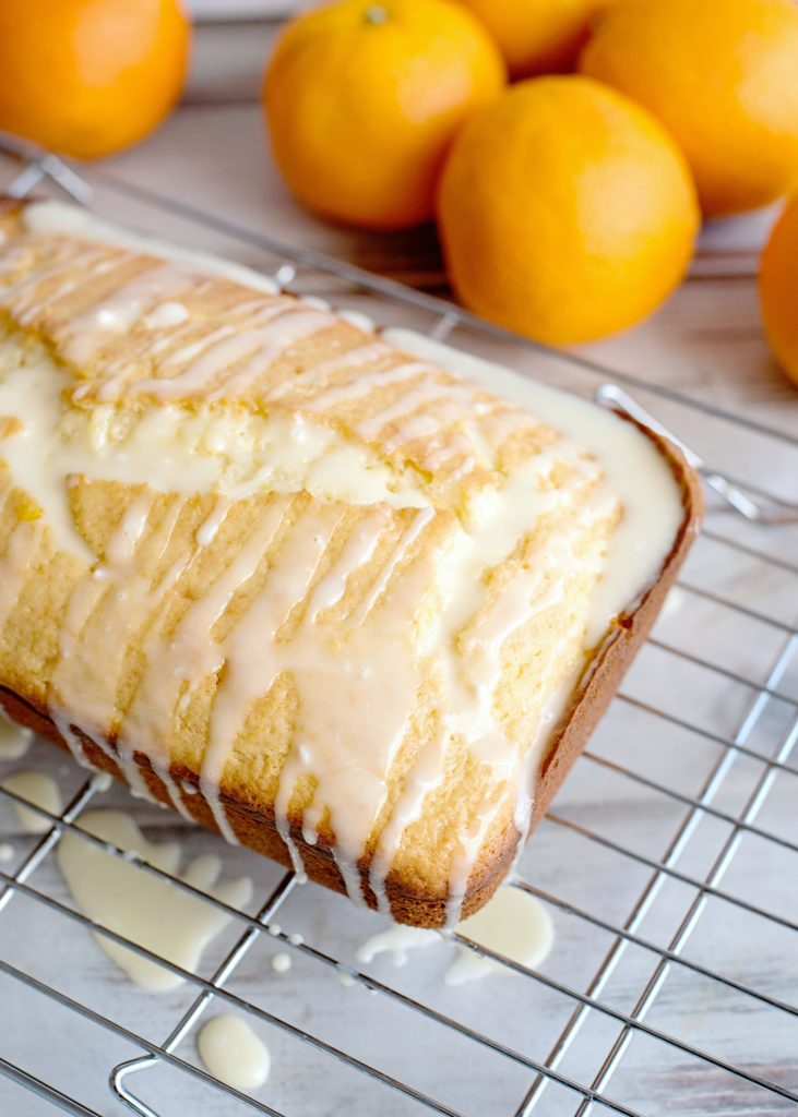 Orange icing glaze poured generously over orange bread on cooling rack with wax paper underneath.