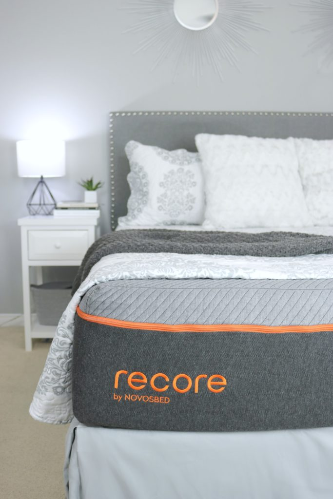 The Recore by Novosbed mattress with blankets folded back to show grey and orange mattress.