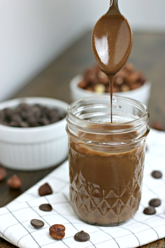 Homemade hazelnut spread in mason jar with spoon lifted above it. It is dripping into mason jar.