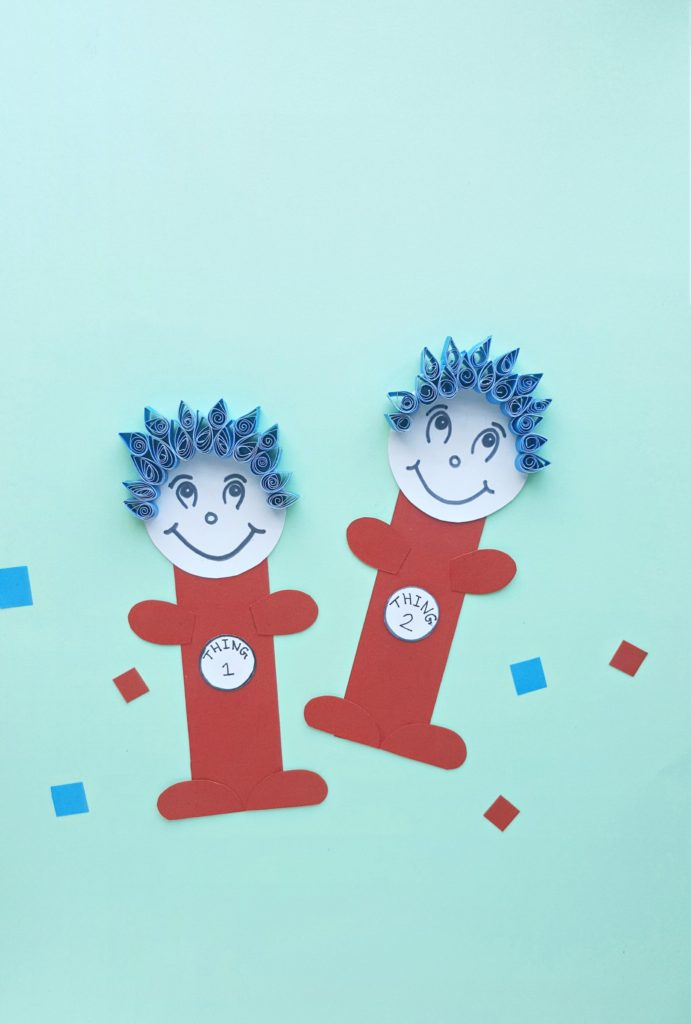 Thing 1 and Thing 2 paper craft are against a teal back drop.