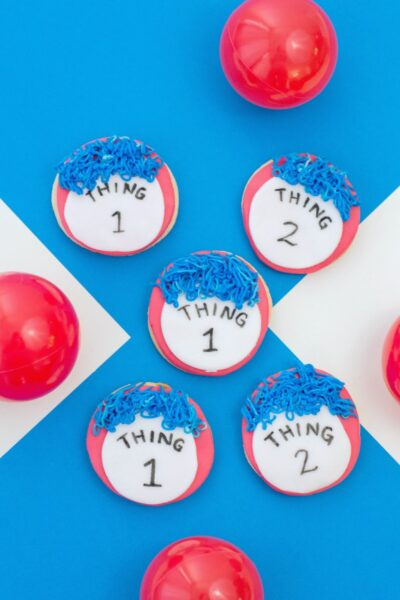 Thing 1 and Thing 2 cookies on a blue and white background, red balls surround it.