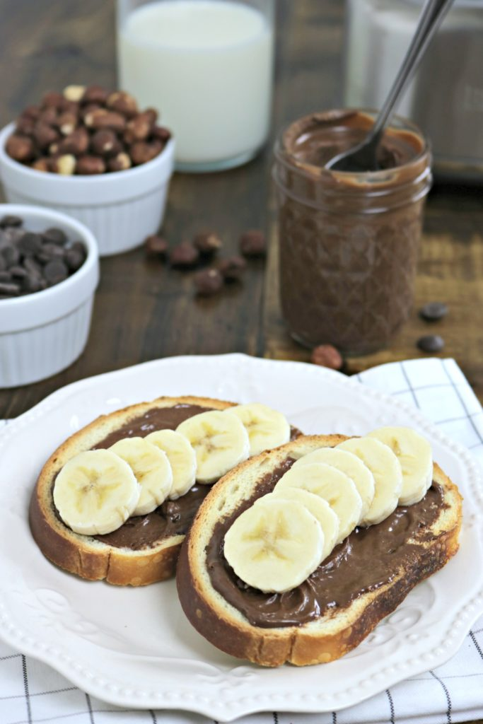 Toast with hazelnut spread and banana on top. Background shows a glass of milk, hazlelnuts, chocolate, and small mason jar with spoon. The Breville Super Q is in the background.