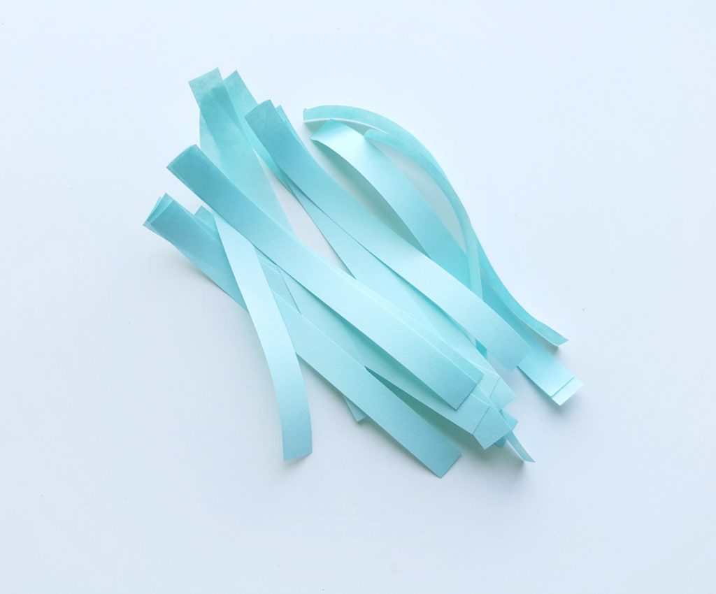 Light blue strips of paper, ready to be quilled.