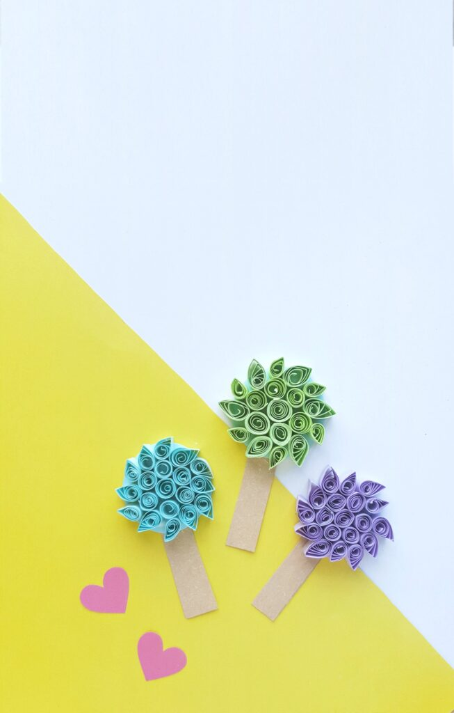 Truffula trees in green, teal, and purple on a yellow and white background with pink hearts surrounding them.