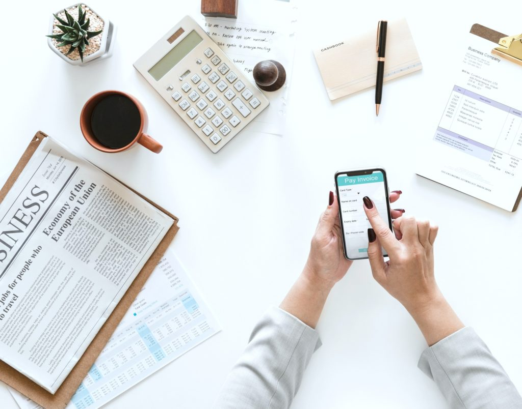 Flatlay view of woman using her smartphone to pay bills. She is surrounded by a calculator, newspaper, pen, paper, coffee, an invoice and a succulent plant.