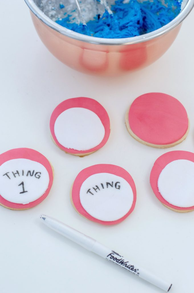 Another smaller white fondant circle is added to the red fondant circle and Thing 1 and Thing 2 is being written on them with a food marker.