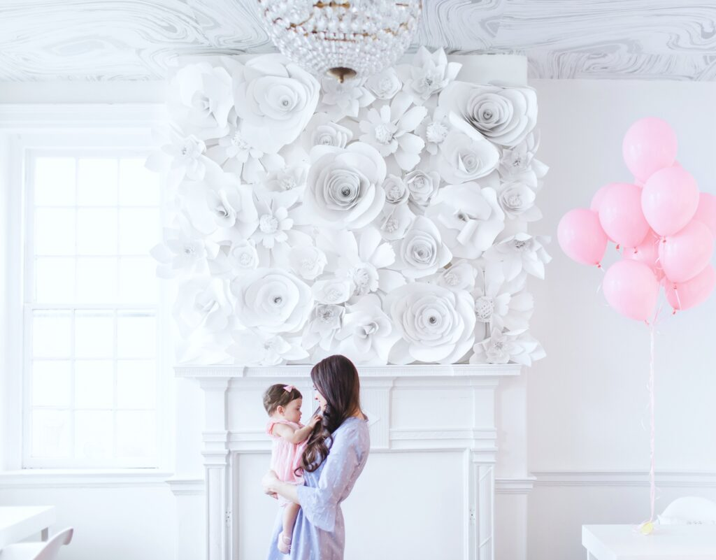 Woman holds a little baby girl in a beautiful white room with flowers and pink balloons.