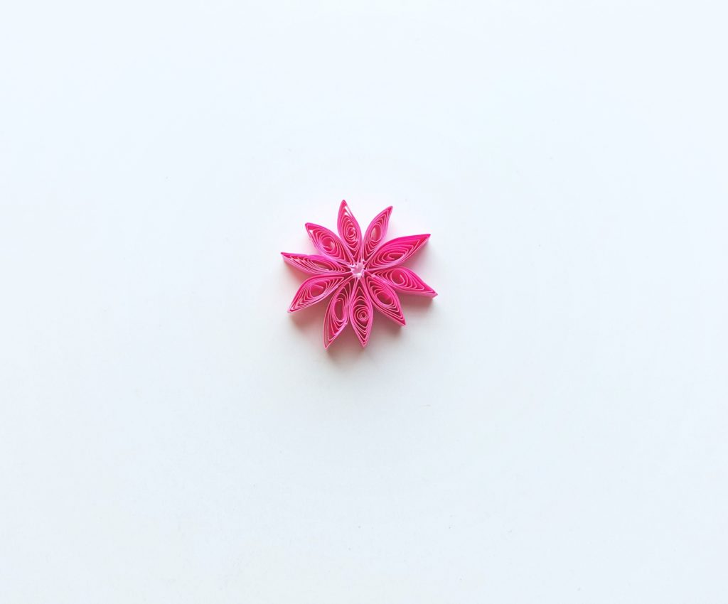 The quilled flower is formed now that all pieces are glued onto the small circle.