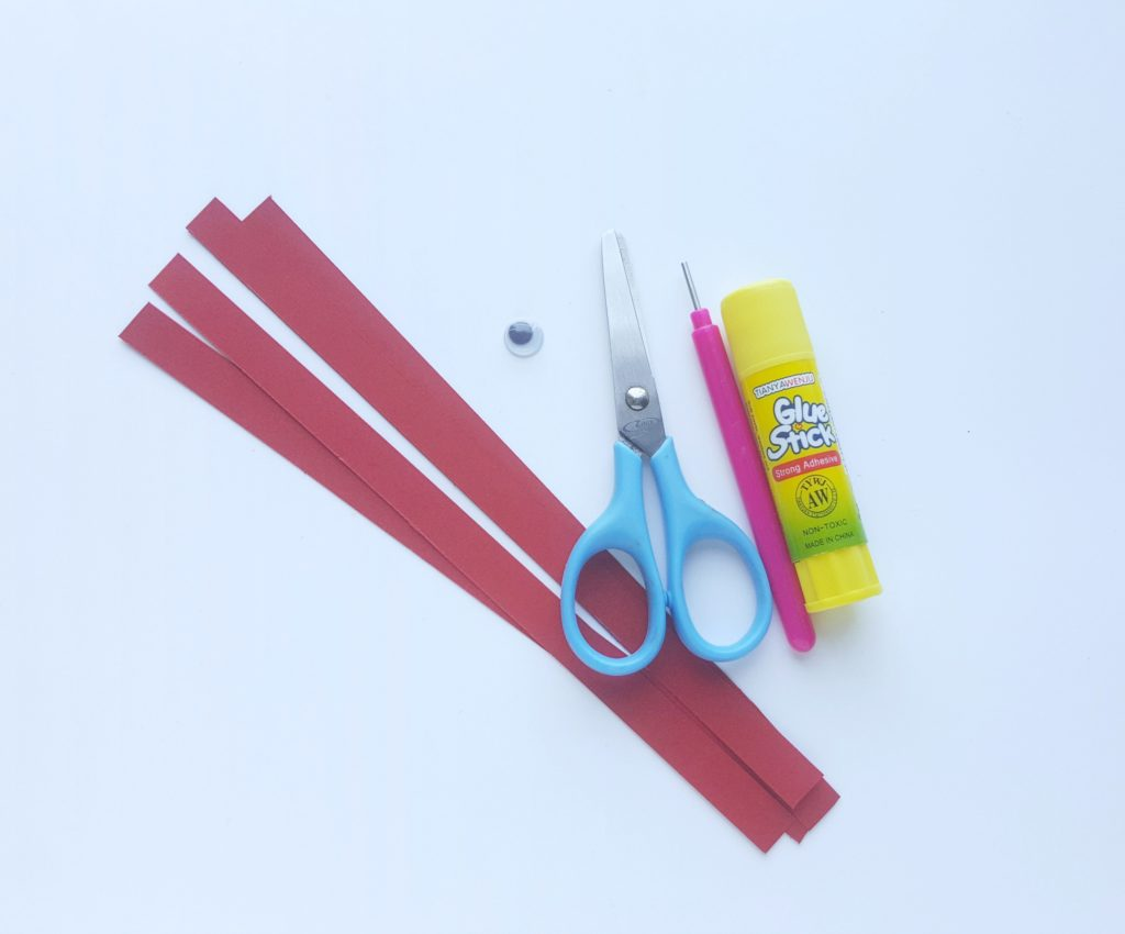 Supplies: Red quilling paper, one googly eye, scissors, glue stick, and quilling tool.