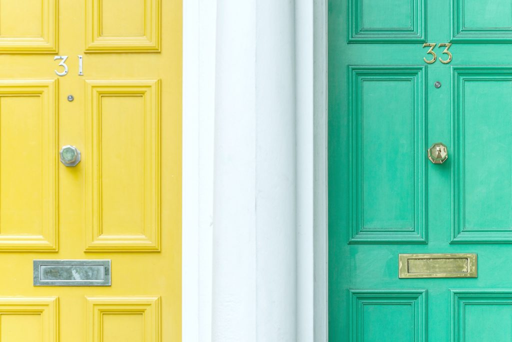 A close up view of a yellow and green door with numbers 31 and 33.