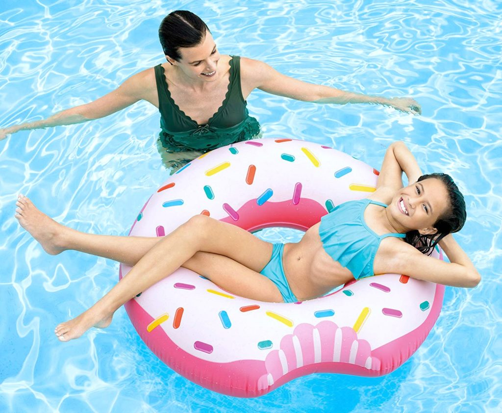 Mom floats with child on a donut pool float.