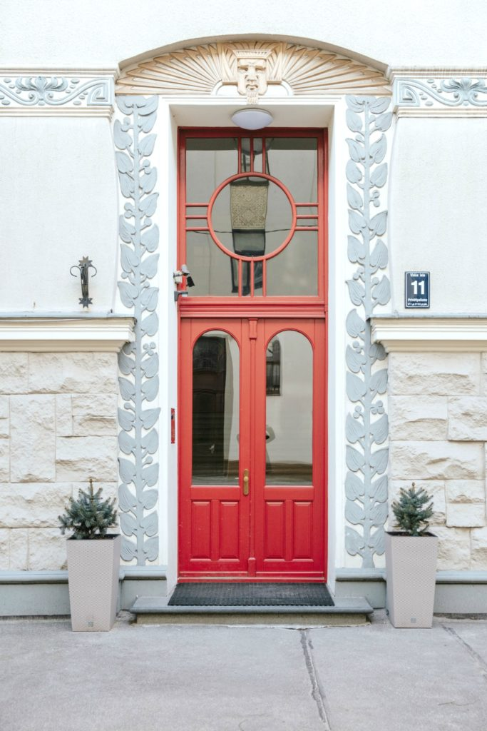A grey and white frame with a bright red door, with two plants lining each side.