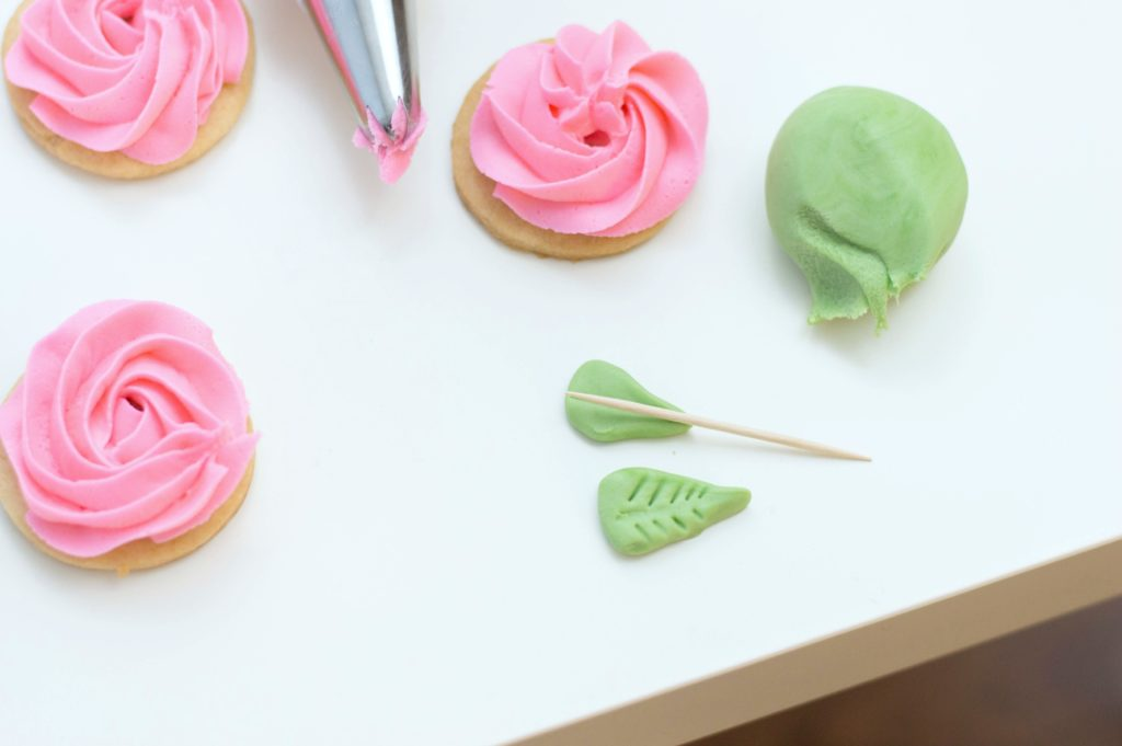 Green fondant leaves are being given detail with toothpicks.