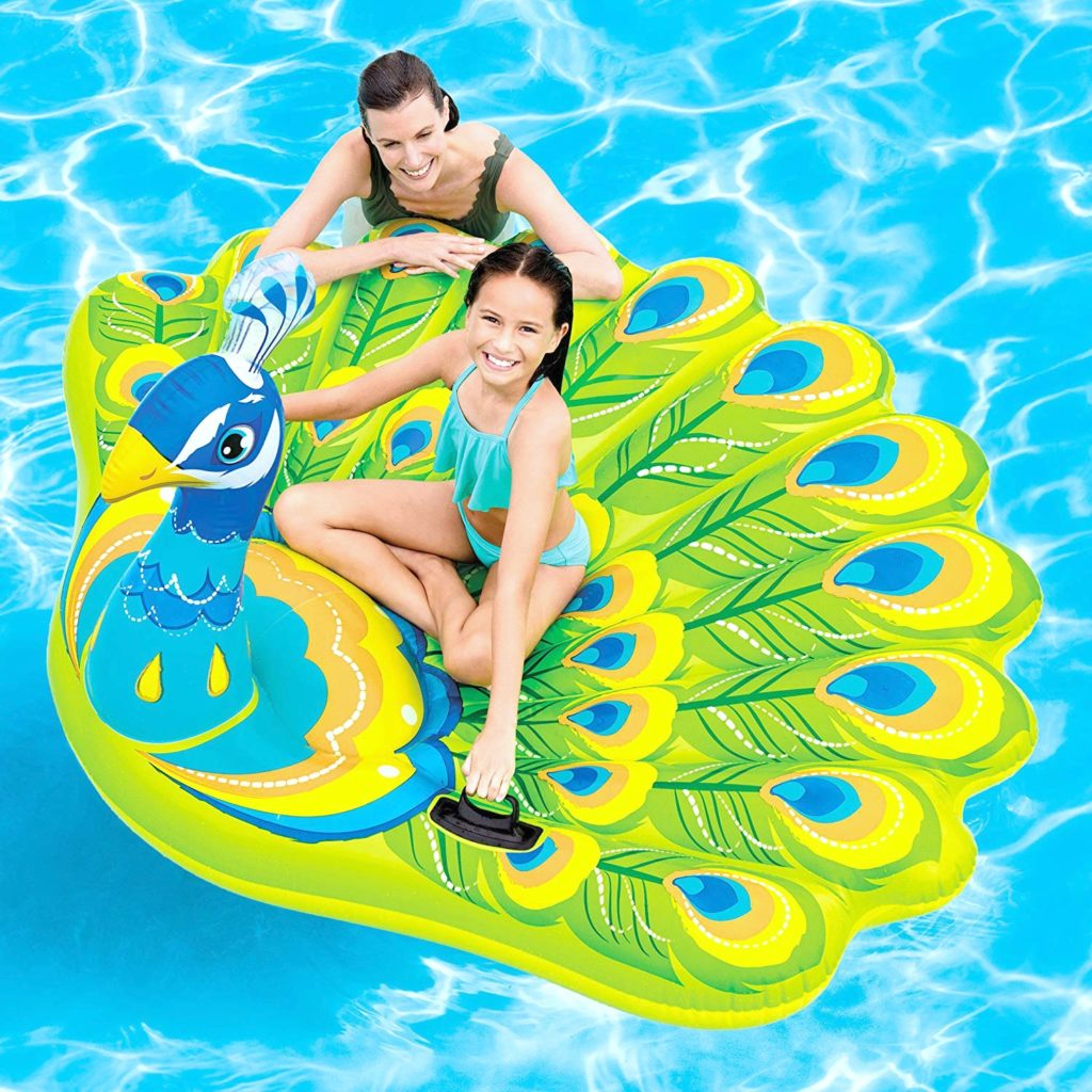 A woman and a girl float in a pool on top of a peacock pool float.