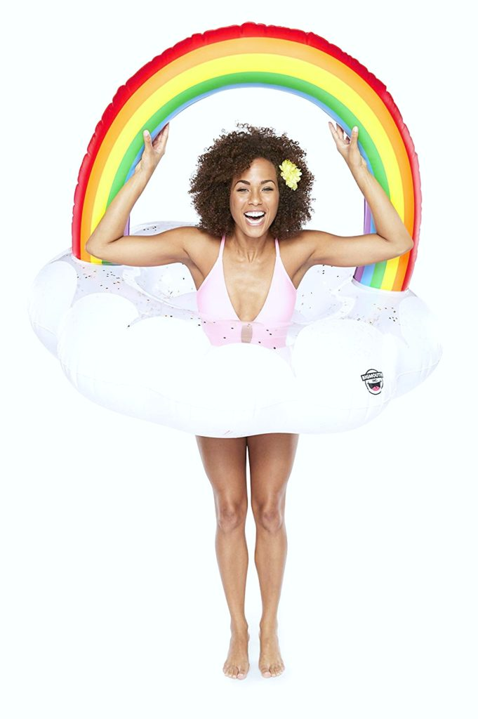 Woman smiling and holding her arms above the rainbow shape above her head of the rainbow pool float.