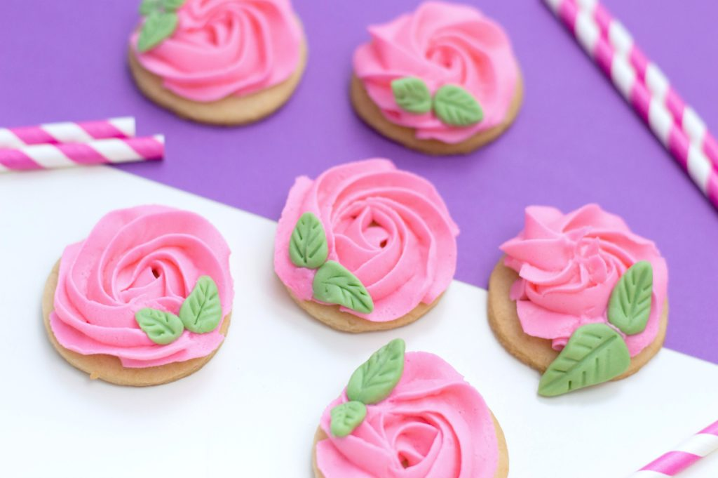 Final product of rose sugar cookies surrounded by purple and white background with pink and white straws.