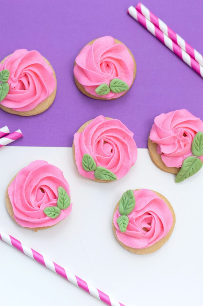A purple and white background with pink rose cookies and pink and white straws.