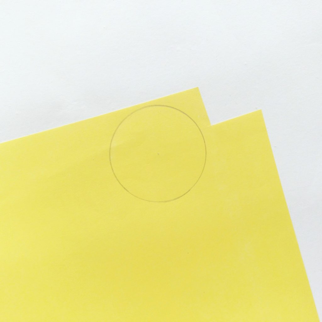 Yellow construction paper with a penciled circle drawn on.