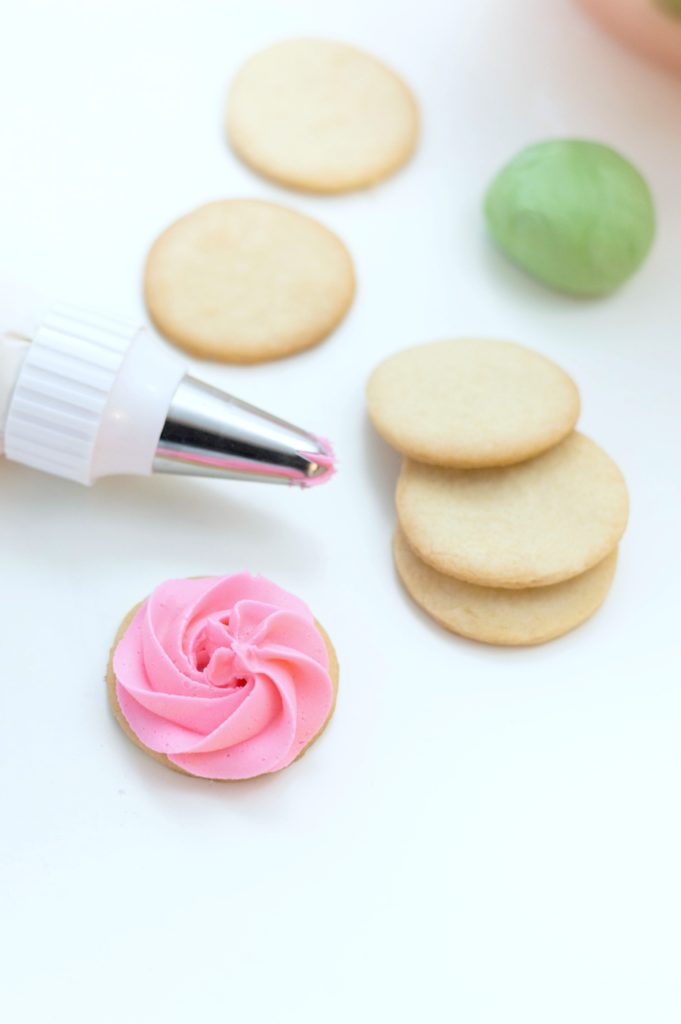 Five cookies, with a green fondant ball and one cookie iced as a rose. A piping bag tip is shown.