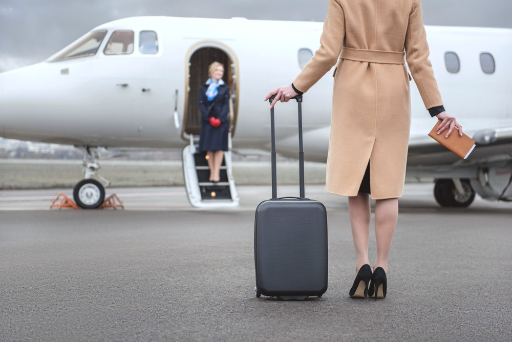 Woman is shown with suitcase about to board private charter jet plane.