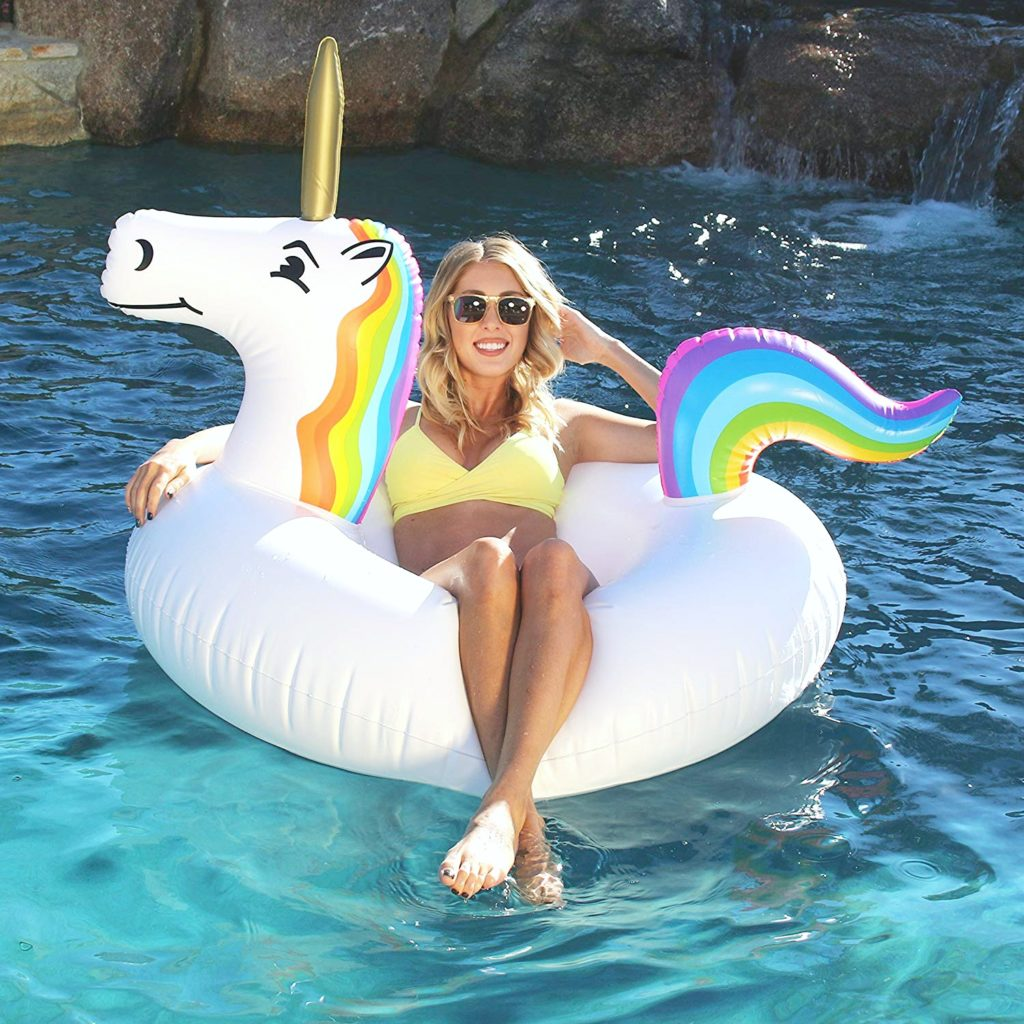 A woman floats on a unicorn pool float in a big pool.