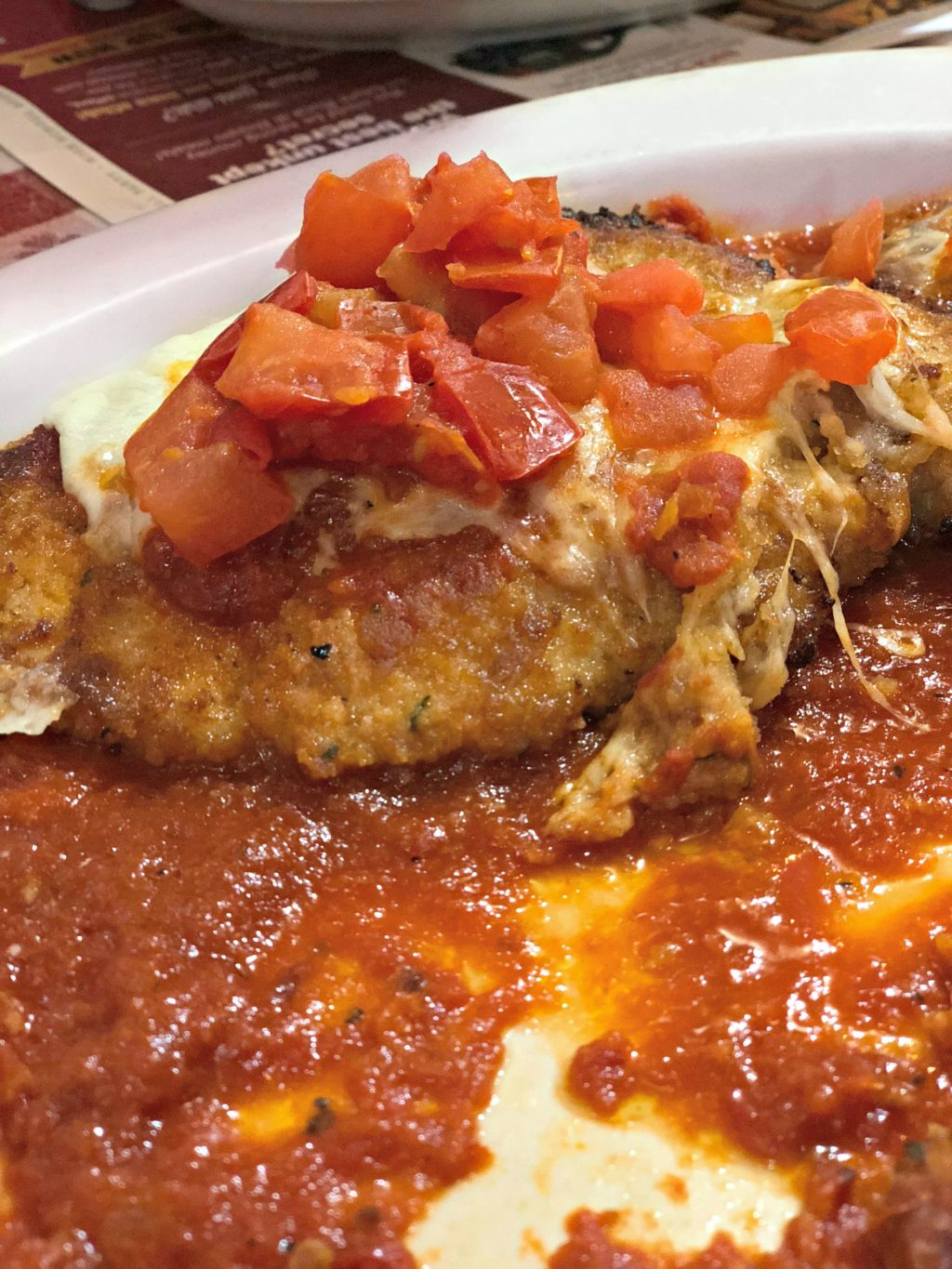A perfectly breaded chicken breast sits atop fresh marinara, topped with fresh diced potato and melted cheese.