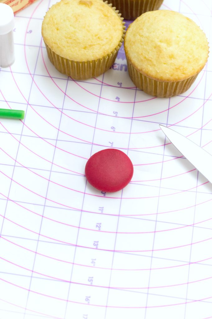 Red fondant ball is flattened on the measuring mat from Wilton.
