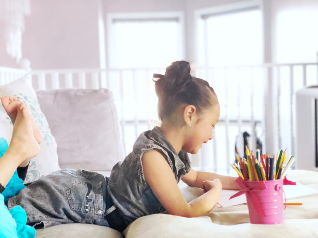Little girl writes and draws happily while laying on couch.