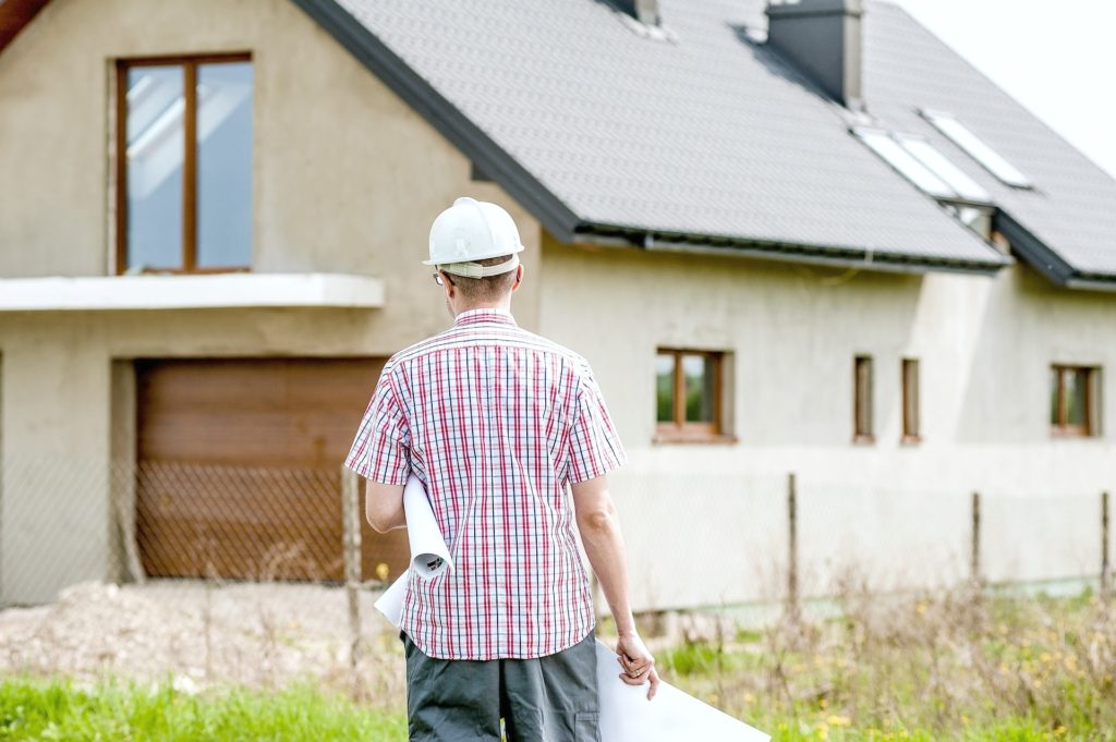 Man with hard hat on is holding building plans and standing in front of a house that is under construction.