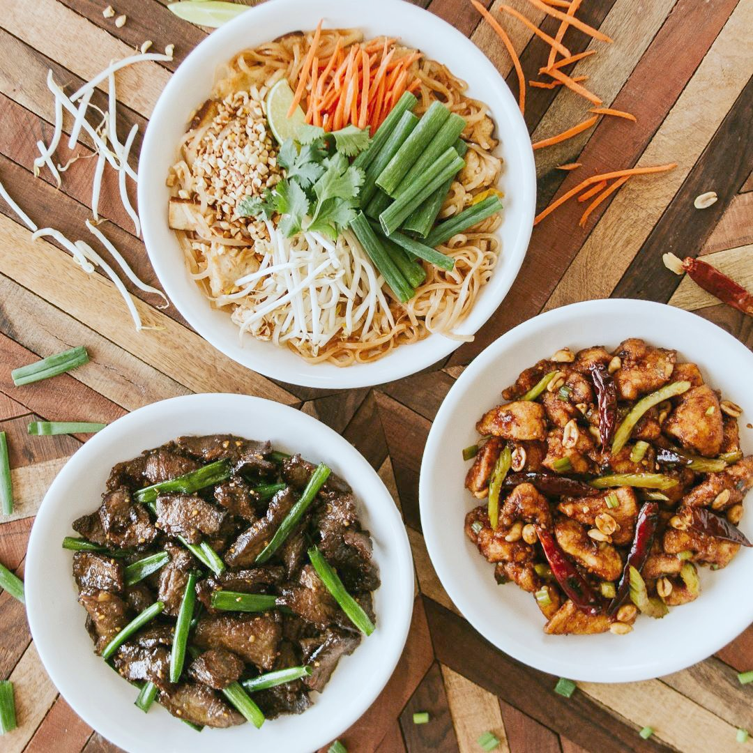 P.F. Chang's most popular entrees on a wooden backdrop.