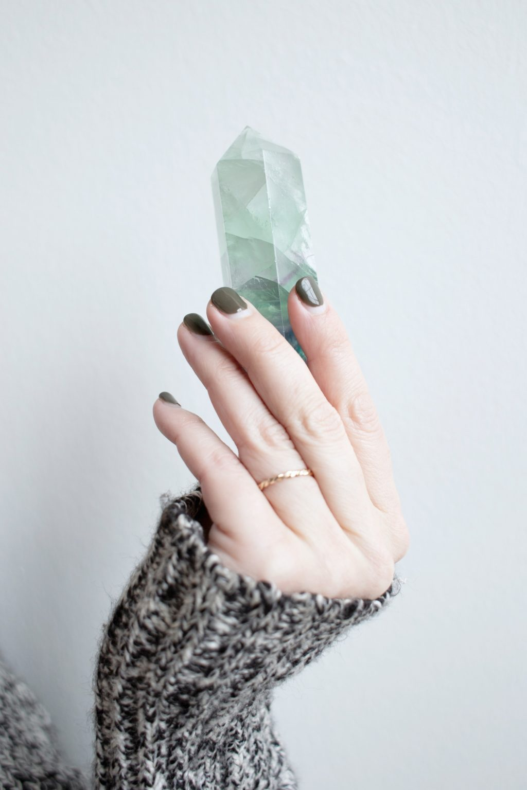 A woman wearing a grey wool sweater is holding a teal/aqua gemstone in her hand.