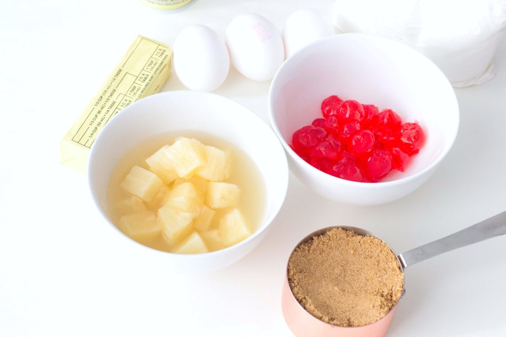 Bowl of diced pineapple and maraschino cherries, eggs, butter, and measured brown sugar are shown.