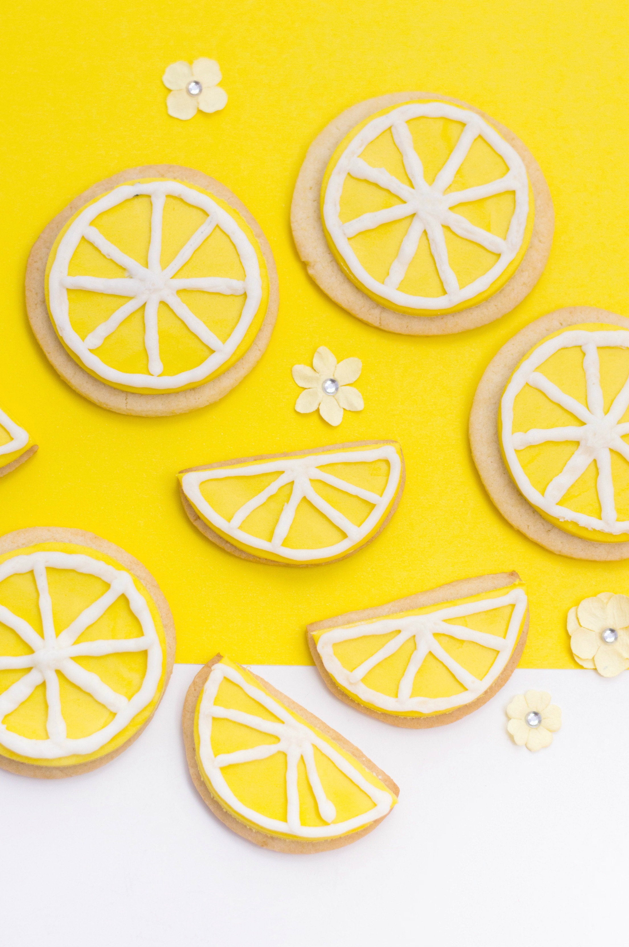 A yellow and white background with sugar cookies and small flowers are shown. 4 are made to look like lemon slices and 4 are cut in half to look like lemon wedges.