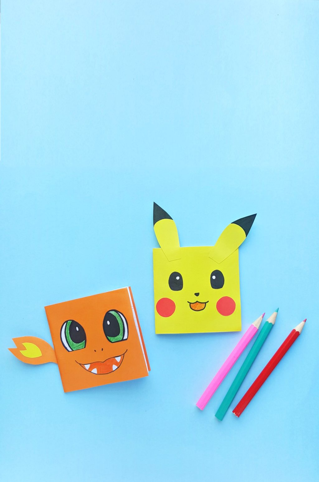 A blue background with DIY Charmander and Pikachu Notebooks with 3 pencil crayons.