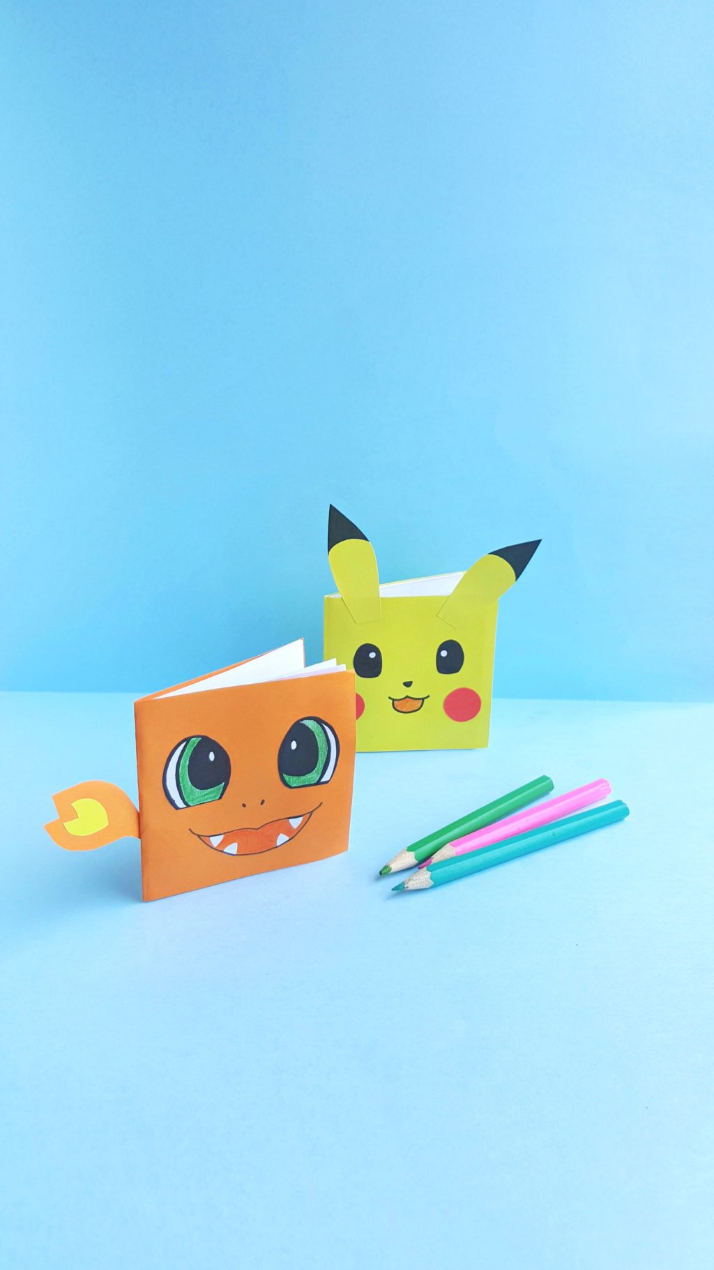 A mini Charmander notebook and Pikachu notebook are shown standing up with coloured pencils.
