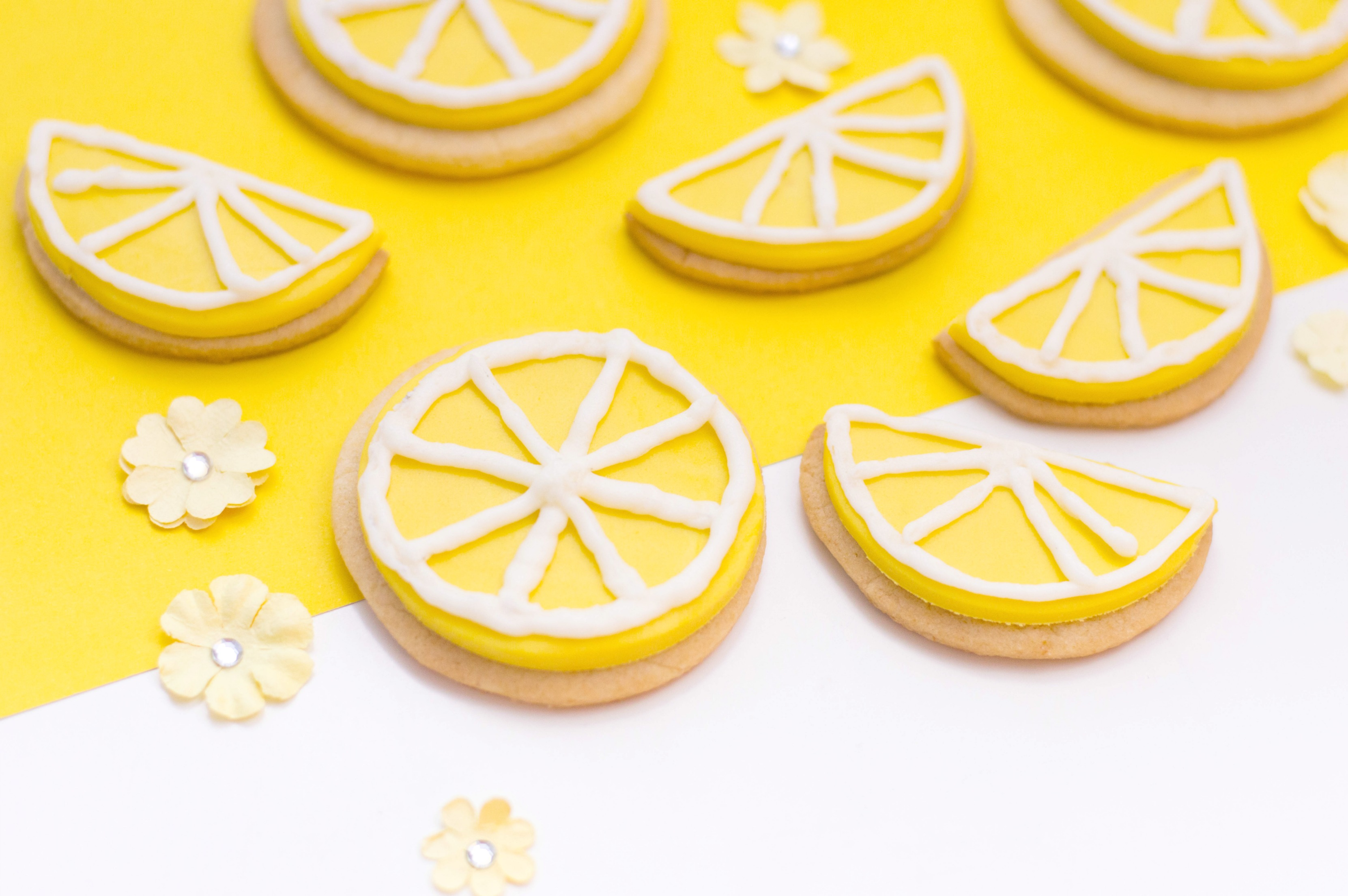 Close up of lemon slices and wedges sugar cookies, iced and ready to eat on a yellow and white background.